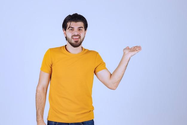 Hombre de camisa amarilla mostrando algo en su mano abierta.