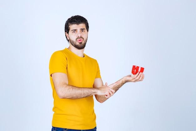 Hombre de camisa amarilla sosteniendo una taza roja y pensando.