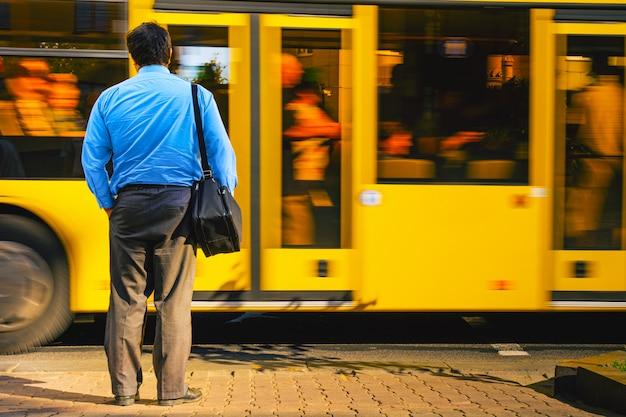 Un hombre con una camisa azul en el bullicio de la ciudad contra un autobús que pasa. hombre cerca de la carretera vista desde la parte posterior. hombre cansado regresa del trabajo de oficina. concepto de rutina de trabajo.