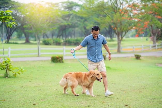 Hombre de la camisa azul caminando el perro golden retriever en el jardín