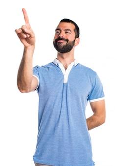 Hombre con la camisa azul que toca en la pantalla transparente