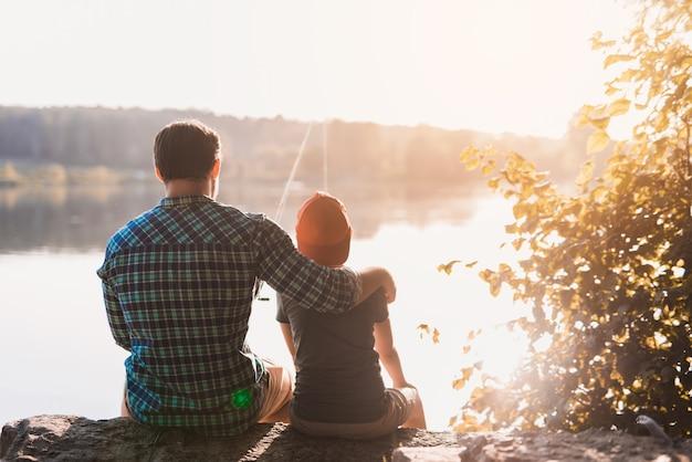 El hombre en una camisa azul se sienta en la orilla del río y abraza a su hijo