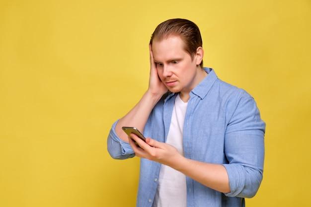 Un hombre con una camisa azul sobre un fondo amarillo mira el teléfono inteligente con una mirada sorprendida.