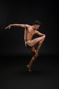 Hombre sin camisa bailando de puntillas