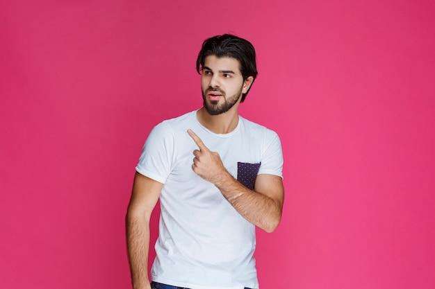 Hombre con camisa blanca apuntando y presentando algo por encima de su cabeza.