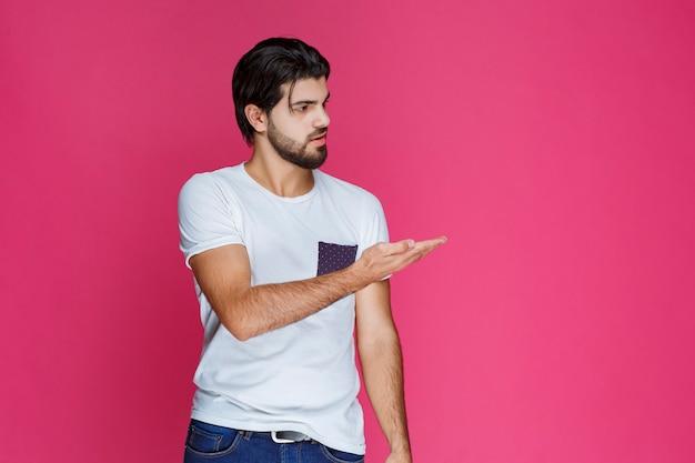 Hombre con camisa blanca apuntando y presentando algo en el lado derecho.