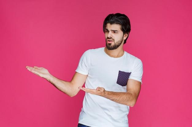 Hombre con camisa blanca apuntando y presentando algo en el lado izquierdo.