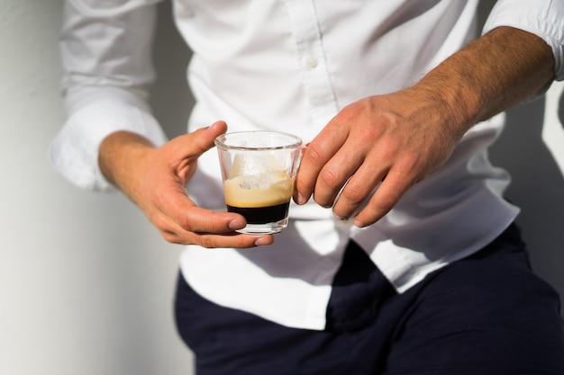 Hombre en camisa blanca bebe café al aire libre en verano