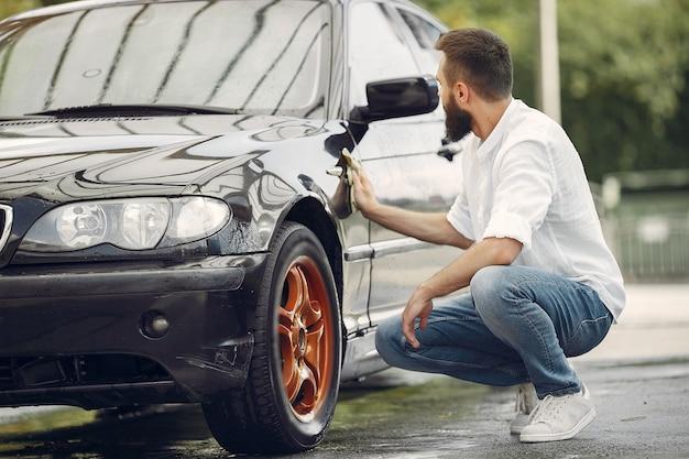 El hombre con una camisa blanca limpia un automóvil en un lavadero de autos