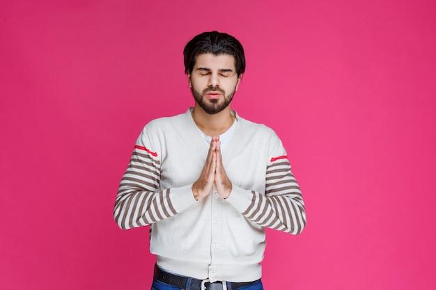 Hombre con camisa blanca rezando o deseando algo.
