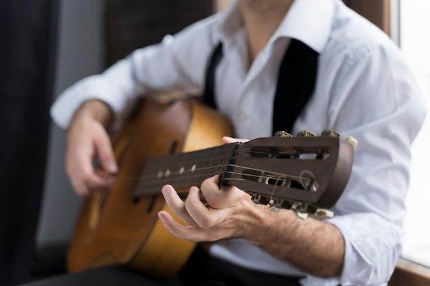 Hombre de camisa blanca tocando el primer plano de la guitarra