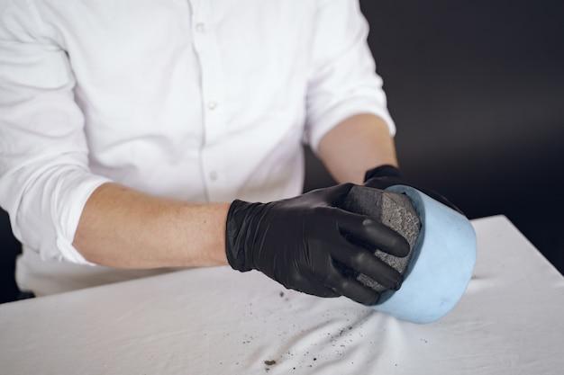 Hombre con camisa blanca trabaja con cemento