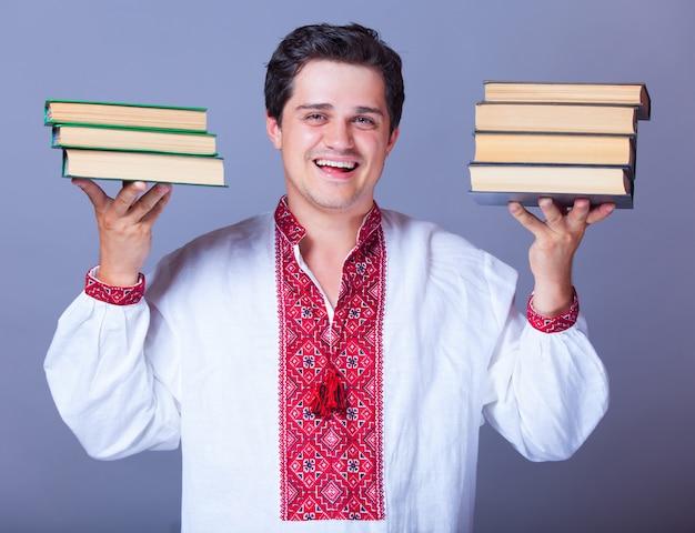 Hombre en camisa bordada con libros.