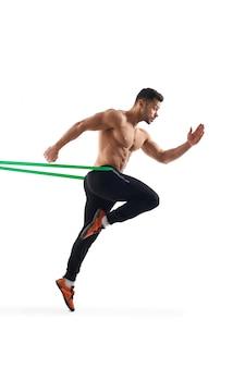 Hombre sin camisa corriendo en su lugar usando una banda de resistencia.