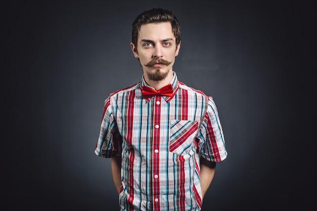 Hombre en camisa a cuadros y pajarita en el estudio