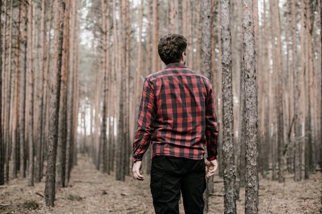 Hombre en camisa a cuadros roja y pantalón militar negro perdido en el bosque de pinos. copia espacio entonado