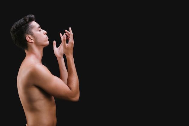 Hombre sin camisa gesticulando durante el baile