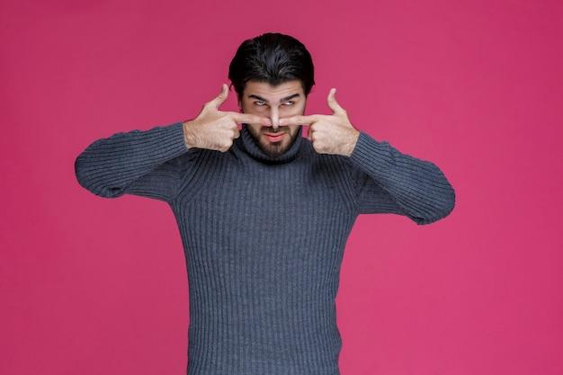 Hombre de camisa gris apuntando su nariz.