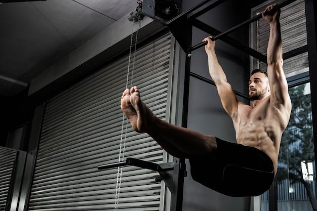 Hombre sin camisa haciendo levantarse en el gimnasio de crossfit