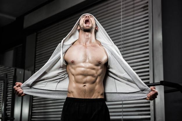 Hombre sin camisa con jersey gris gritando en el gimnasio de crossfit