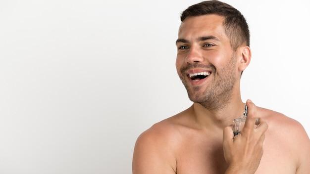 Hombre sin camisa joven feliz rociando perfumes de pie contra el fondo blanco.