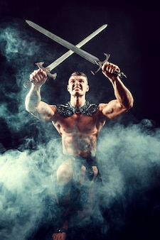 Hombre sin camisa musculoso posando ferozmente con espadas