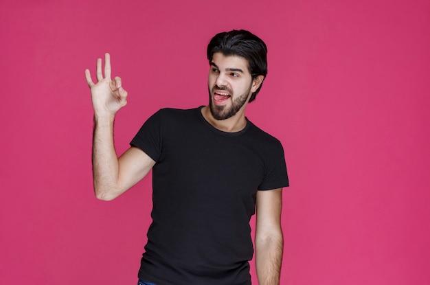 El hombre con camisa negra muestra que está disfrutando completamente de algo