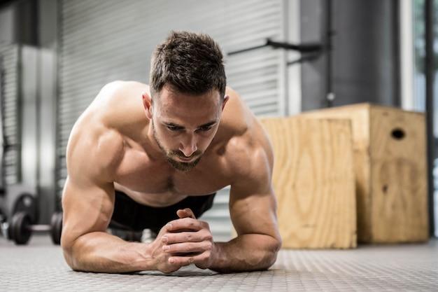 Hombre sin camisa planchas en el gimnasio de crossfit