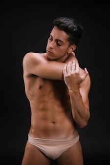 Hombre sin camisa que estira el cuello y el brazo