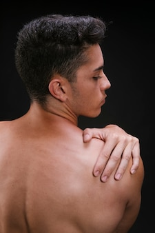 Hombre sin camisa que estira los músculos del hombro