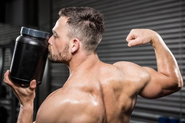 Hombre sin camisa que muestra bíceps y besos puede en el gimnasio de crossfit
