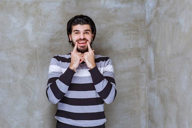 Hombre con camisa a rayas apuntando a su boca o sonrisa
