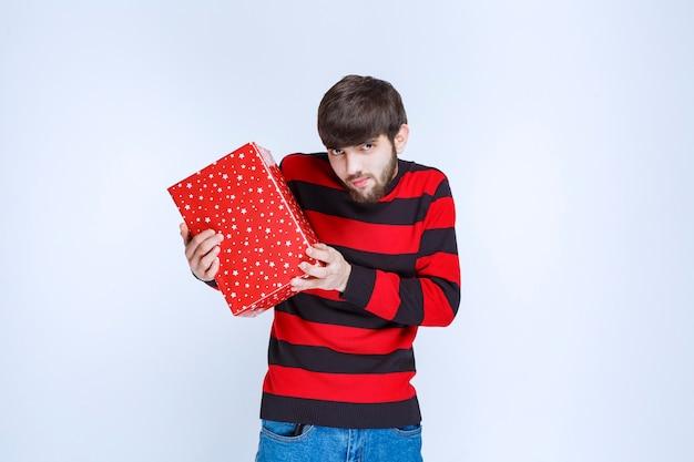 Hombre de camisa a rayas rojas con una caja de regalo roja y ofreciéndola