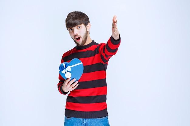 Hombre con camisa de rayas rojas sosteniendo una caja de regalo con forma de corazón azul y llamando o notando a alguien más adelante.