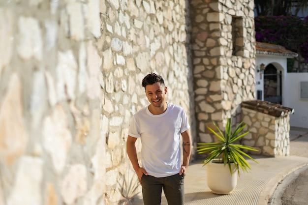 Un hombre con una camisa a rayas, con un sombrero de paja, camina por las calles de un pequeño pueblo español.