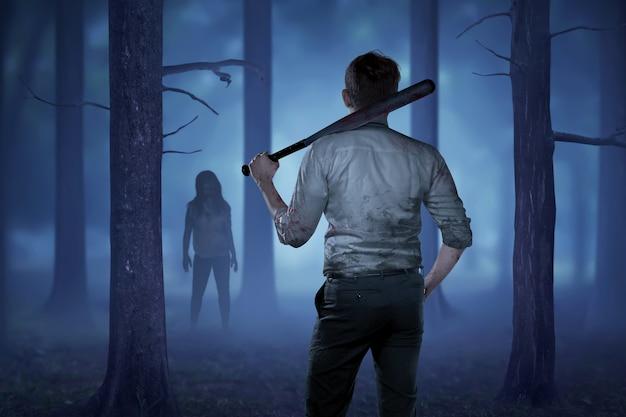 El hombre en una camisa sangrienta sosteniendo un palo sangriento quiere golpear a la dama zombie