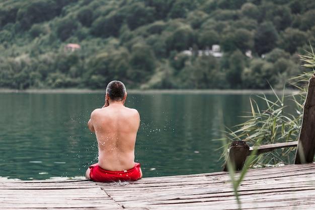 Hombre sin camisa sentado en el muelle de madera cerca del lago