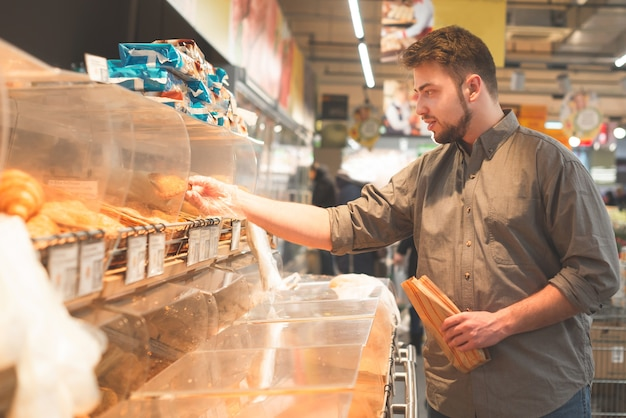 El hombre con una camisa sostiene una bolsa de papel en sus manos, se para en el departamento de pan del supermercado y selecciona bollos.
