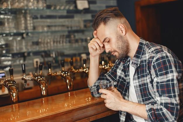 El hombre con una camisa tiene un vaso en sus manos. guy está sentado en la barra y sosteniendo su cabeza.