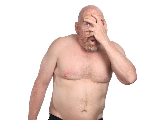 Hombre sin camisa tímido sobre fondo blanco.