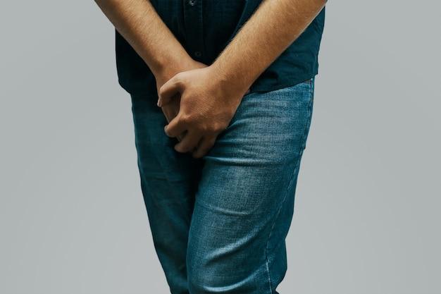 El hombre en una camisa verde y pantalones vaqueros siente dolor en la entrepierna que se esconde detrás de sus manos