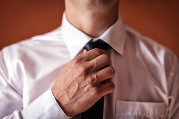 Hombre en camisa vestirse y ajustar corbata en el cuello en casa