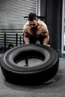 Hombre sin camisa volteando neumático pesado en el gimnasio de crossfit