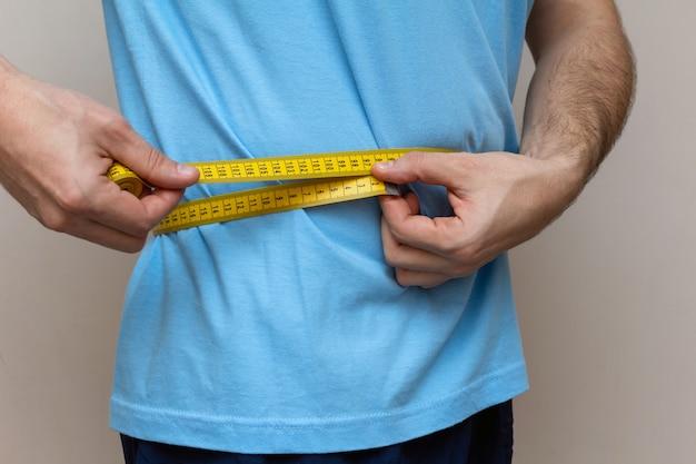 El hombre con una camiseta azul mide la cintura con una cinta amarilla.