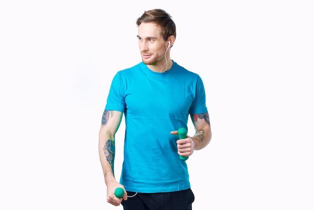 Hombre en camiseta azul con pesas en la mano tatuaje entrenamiento de fitness