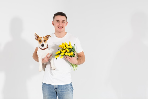 Hombre en camiseta blanca de pie con flores y perro. hombre romántico con ramo de tulipanes para cumpleaños. feliz dia de la mujer. dando ramo de flores. hombre guapo dando flores. fondo blanco.