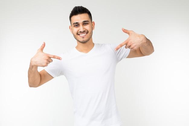 Hombre con una camiseta blanca en una plantilla en blanco sobre un fondo blanco de estudio.