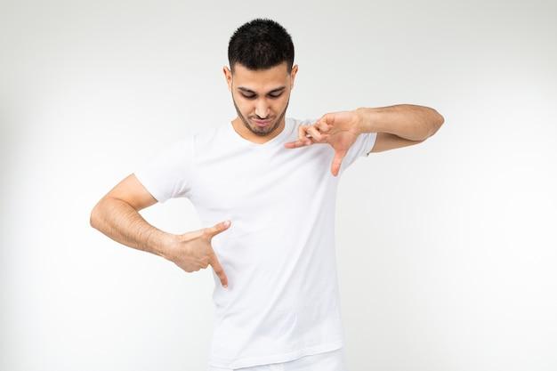 Hombre con una camiseta blanca con una plantilla para imprimir sobre un fondo blanco de estudio.