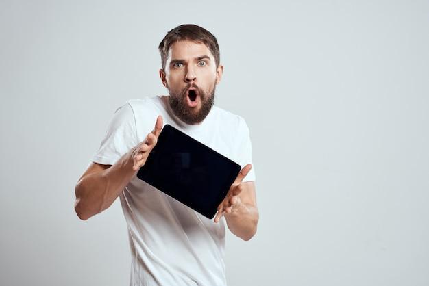 Un hombre con una camiseta blanca con una tableta electrónica en sus manos