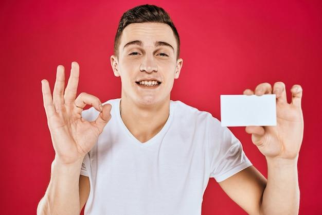 Un hombre con una camiseta blanca con una tarjeta de presentación en sus manos emociones fondo rojo